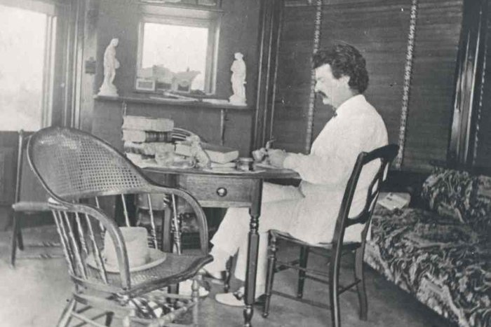 || Mark Twain sitting at his desk.